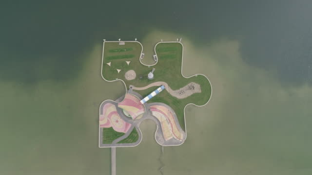 aerial shot moving up whilst looking down on a puzzle piece shaped playground in a lake, utrecht, netherlands - puzzle stock videos & royalty-free footage