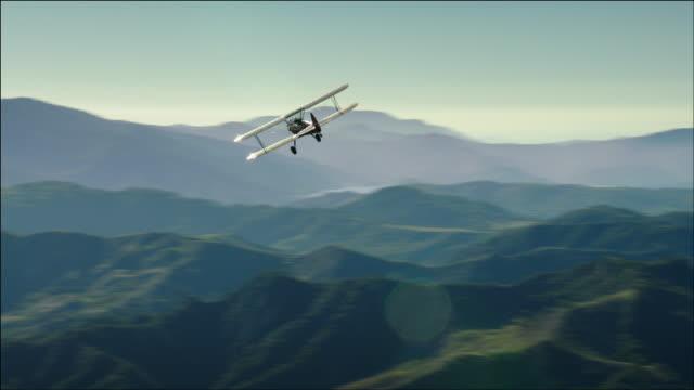 vidéos et rushes de aerial shot of 1941 pt-17 stearman biplane, flying over beautiful green rolling hills and valleys near ventura, ca - biplan
