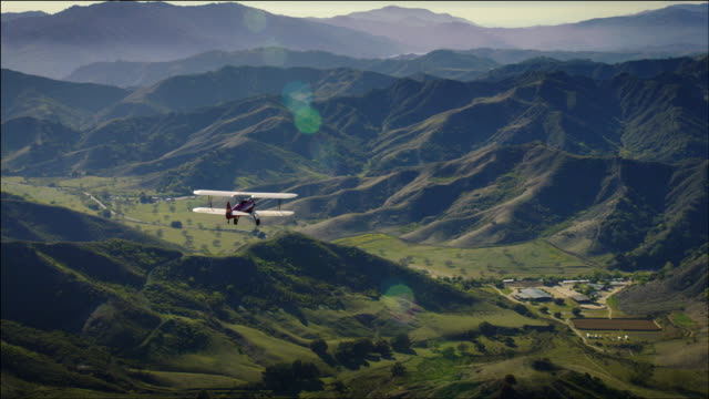 Aerial shot of 1941 PT-17 Stearman biplane, flying over beautiful green rolling hills and valleys near Ventura, CA