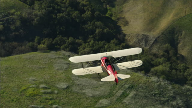 vidéos et rushes de aerial shot of 1941 pt-17 stearman biplane, seen from above, flying over beautiful green rolling hills and lake casitas near ojai, ca - biplan