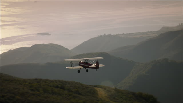 aerial shot of 1941 pt-17 stearman biplane, sun glinting off the wings, flying over hills toward the pacific ocean,near ventura, ca - ventura stock videos and b-roll footage