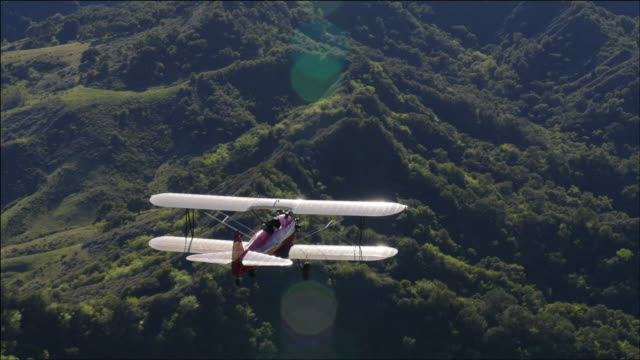 vidéos et rushes de aerial shot of 1941 pt-17 stearman biplane, with sun glinting off the wings, flying over green rolling hills near ventura, ca - biplan