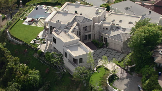 stockvideo's en b-roll-footage met los angeles, california - march 30, 2011: aerial shot of 9161 oriole way in the hollywood hills. the mansion, owned by hip hop mogul dr dre circa 2011, offers a commanding view from its perched location. - landhuis