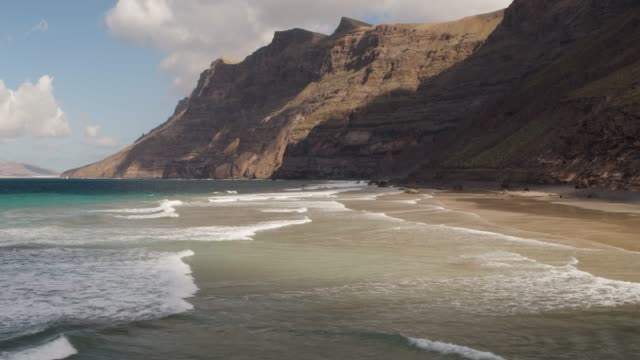 aerial shot of a beach and mountains in lanzarote - spain stock videos & royalty-free footage