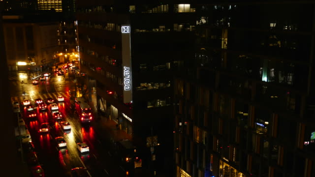 """aerial shot of a busy city street at night; sign """"dolby""""; cars waiting for the light at the intersection; surrounded by tall buildings and city lights - northern california stock videos & royalty-free footage"""