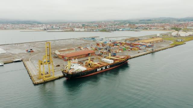 vidéos et rushes de tir aérien d'un cargo dans le port - décharger