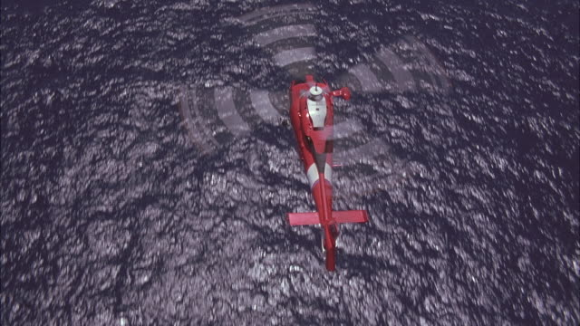 aerial shot of a coast guard chopper flying over an ocean. - hubschrauber stock-videos und b-roll-filmmaterial