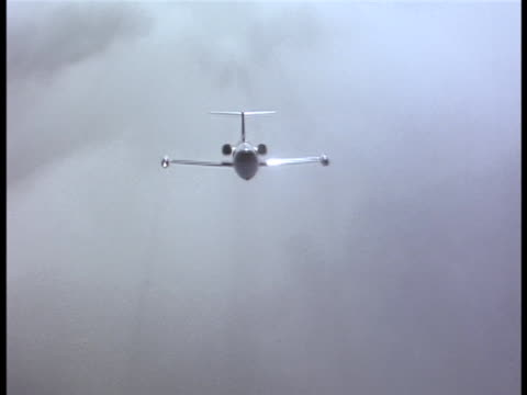 aerial shot of a corporate lear jet flying through cloud banks. - air to air shot stock videos and b-roll footage