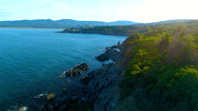 vídeos de stock, filmes e b-roll de tiro aéreo de um avião voando sobre falésias e mar de água e para viaja resort - bulgária
