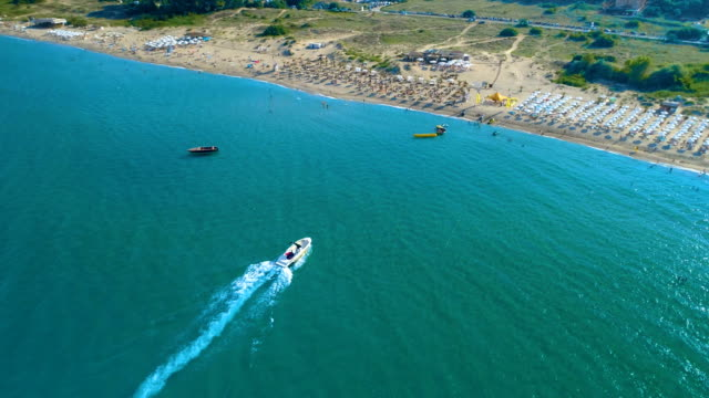 Aerial shot of a drone following a boat in the sea and then flies away