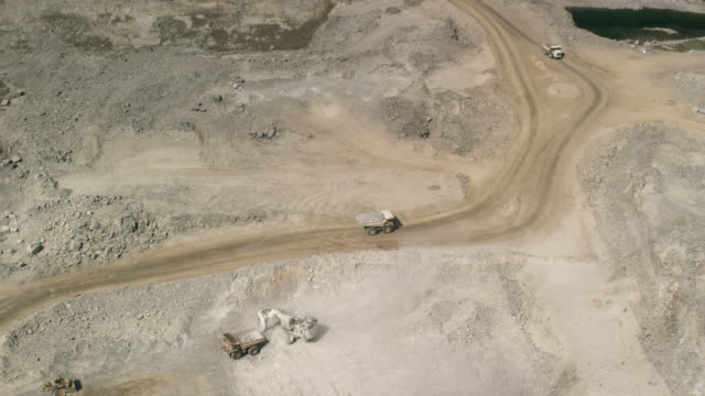aerial shot of a dump truck removing rubble on a mine - rubble stock-videos und b-roll-filmmaterial