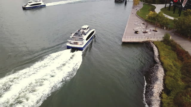 vidéos et rushes de aerial shot of a ferry landing at the shore of long island city, queens. - ferry