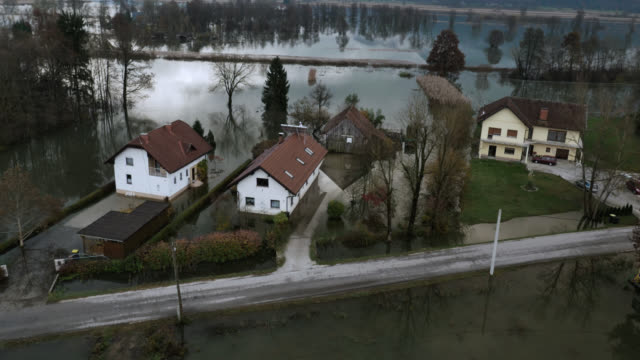 Aerial shot of a few houses surrounded by flood