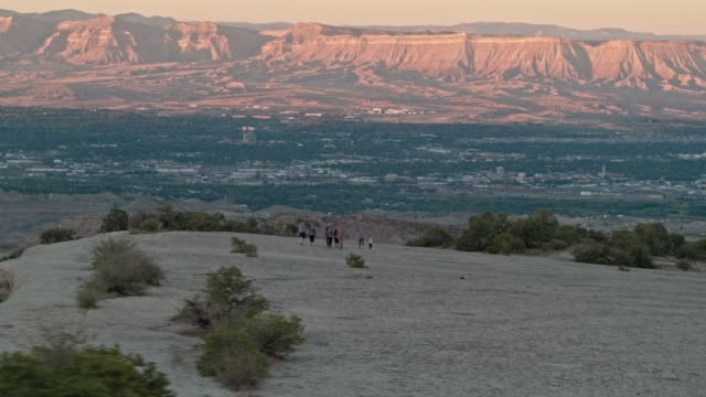 aerial shot of a group of thirty-something people hike together in the desert of the colorado national monument over grand junction, colorado overlooking the bookcliffs at sunset - colorado stock videos & royalty-free footage