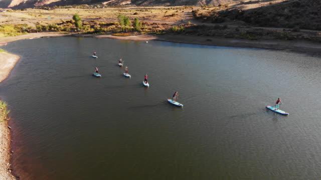 luftaufnahme von einer gruppe von frauen, paddeln in folge auf paddleboards auf einem wüste see an einem sonnigen tag im westlichen colorado (snooks unten) - colorado westliche bundesstaaten der usa stock-videos und b-roll-filmmaterial