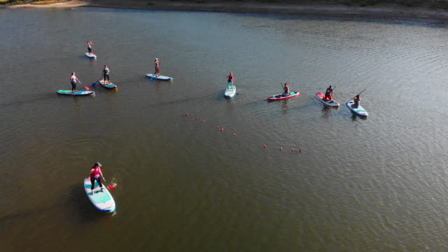 aerial shot of a group of women paddling on paddleboards on a desert lake on a sunny day in western colorado (snooks bottom) - early morning exercise stock videos & royalty-free footage