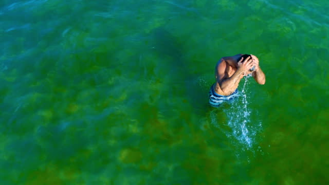 aerial shot of a handsome man walking out of the sea water after swim - aircraft point of view stock videos & royalty-free footage