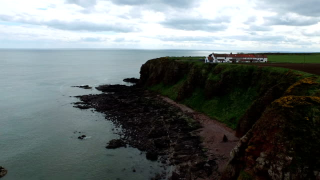 Aerial shot of a house close to cliff edge off the coast of Scotland