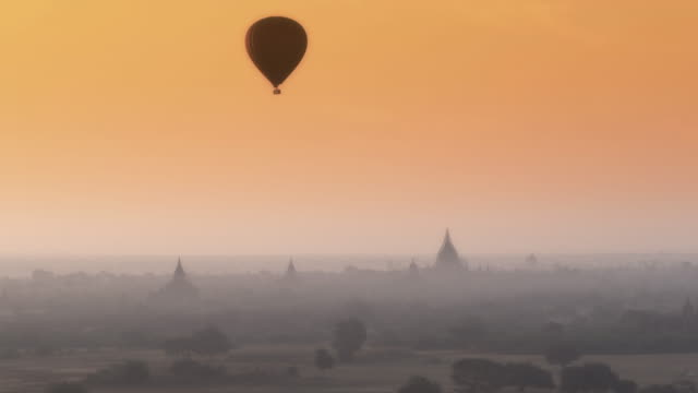 Aerial shot of a lone hot air balloon at sunrise with pagodas in background