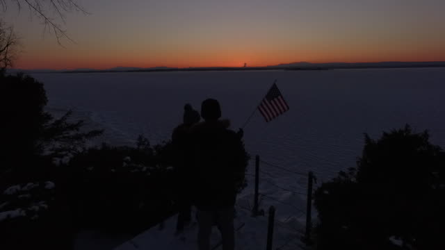 4K aerial shot of a man holding an American flag near a frozen Lake Champlain in Vermont in the winter