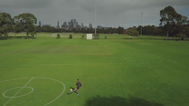 aerial shot of a man training/playing soccer - football pitch stock videos & royalty-free footage