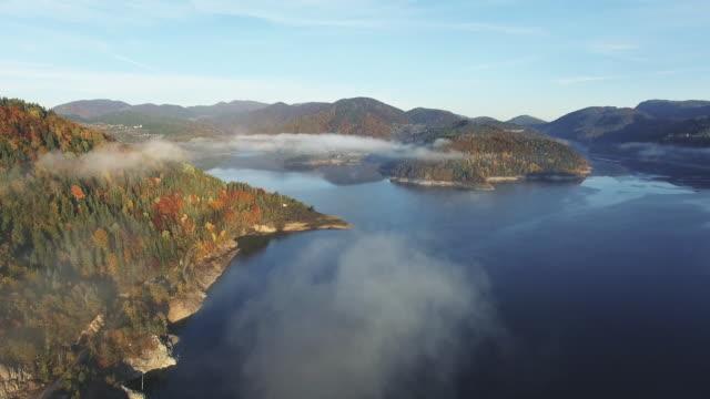 vidéos et rushes de tir aérien d'un lac de montagne. point de vue de drone, montagne de tara en serbie au brouillard. - serbie