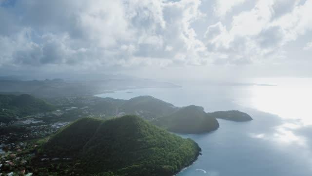 vidéos et rushes de aerial shot of a mountainous coast with a town and blue sea (saint lucia) - arbre tropical