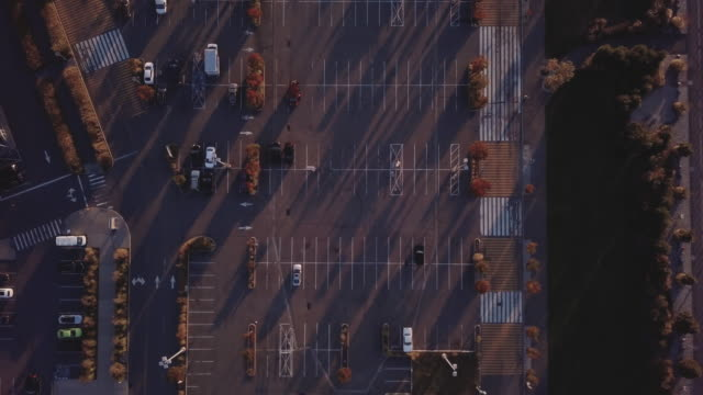 aerial shot of a nearly empty parking lot at sunset. - empty road stock videos & royalty-free footage