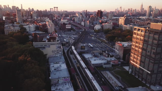 aerial shot of a new york city subway passing through brooklyn at sunset - brooklyn new york stock videos & royalty-free footage