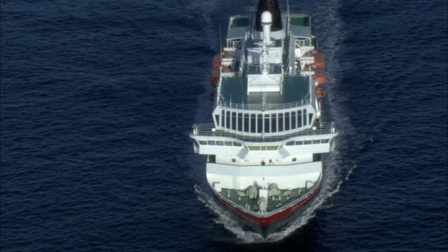Aerial shot of a passenger ship sailing along the coast of western Norway.