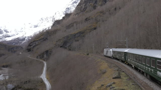 Aerial shot of a passenger train travelling through the Norweigan countryside.