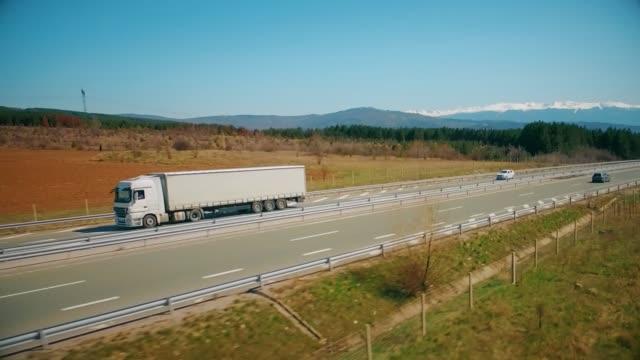 luftaufnahme einer malerischen autobahnstraße - heavy goods vehicle stock-videos und b-roll-filmmaterial