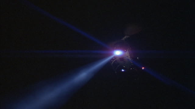 Aerial shot of a police helicopter flying with its searchlight on.