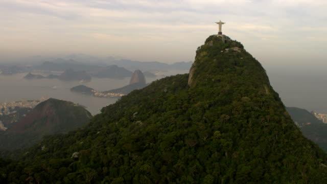 Aerial shot of a religous statue, mountains, buildings, and ocean - Rio de Janeiro, Brazil.