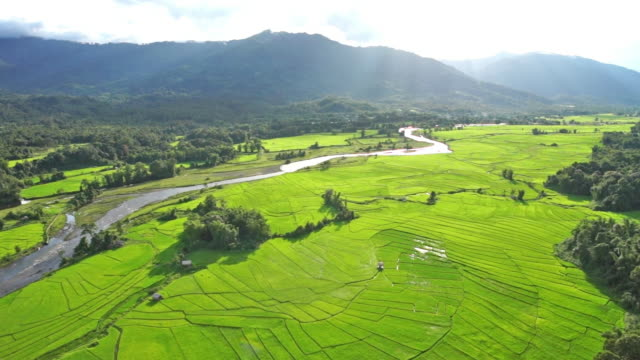 Aerial shot of a river, rice patties, and green mountains in Putao, Myanmar