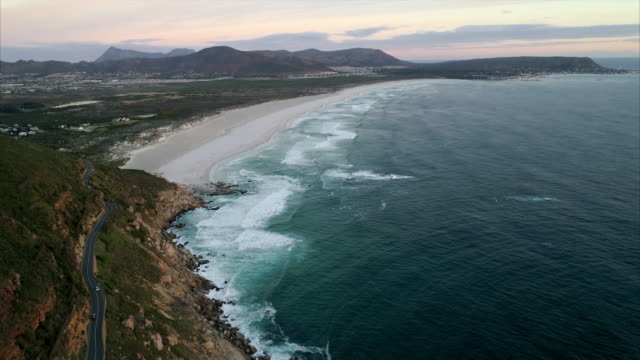 aerial shot of a scenic coastal road on an amazing mountain, drone flying forward while tilting up showing town in the distance - cape town, south africa - town stock videos & royalty-free footage