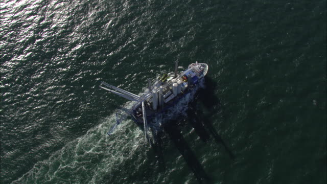 Aerial shot of a ship transporting sections of a turbine to a wind farm off the coast of Denmark.