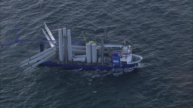 aerial shot of a ship transporting sections of a turbine to a wind farm off the coast of denmark.  - installing stock videos & royalty-free footage