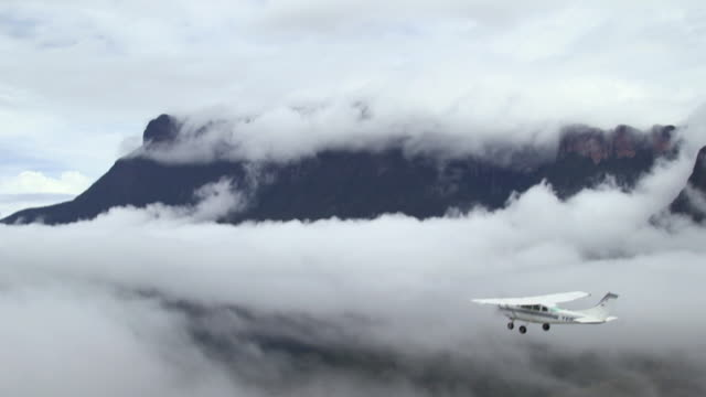 Aerial shot of a small aeroplane flying through clouds in the Tepuis, Venezuela.