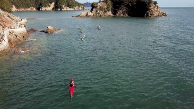 vídeos y material grabado en eventos de stock de toma aérea de un pequeño grupo de kayak de mar de gente - kayak barco de remos