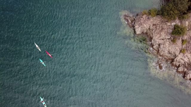 aerial shot of a small group of people sea kayaking - pacific ocean stock videos & royalty-free footage