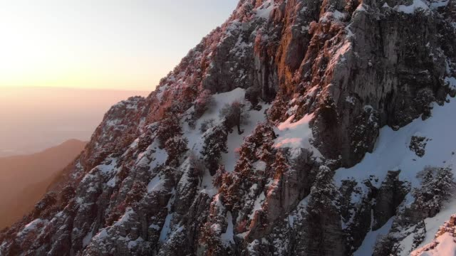 aerial shot of a snowy mountain at sunset - 30 seconds or greater stock videos & royalty-free footage