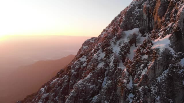 aerial shot of a snowy mountain at sunset - twilight stock videos & royalty-free footage
