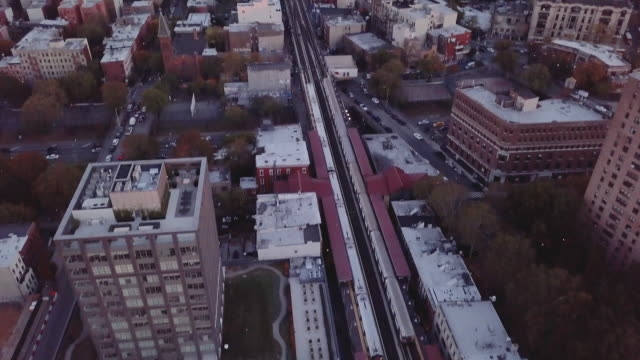 aerial shot of a subway car passing through brooklyn, new york city. - bahngleis stock-videos und b-roll-filmmaterial