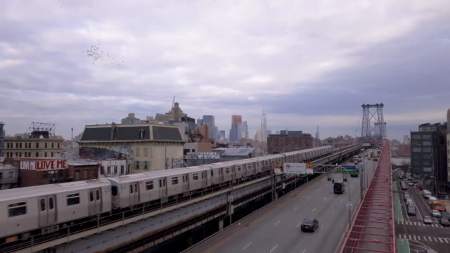 vídeos de stock, filmes e b-roll de aerial shot of a subway train passing over brooklyn's williamsburg bridge - brooklyn new york