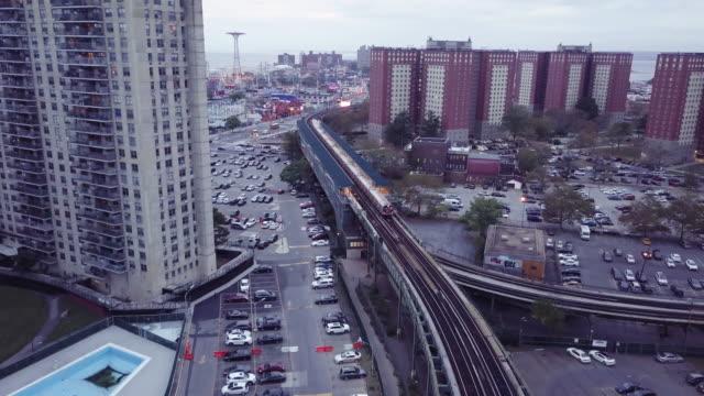 aerial shot of a subway train passing through coney island, brooklyn. - coney island stock videos & royalty-free footage