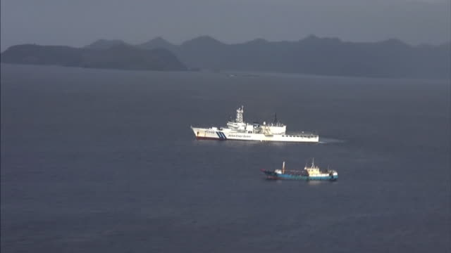 Aerial shot of a suspicious boat and a Japan Coast Guard ship sailing together within the area of Japanese waters where Chinese illegal coral...