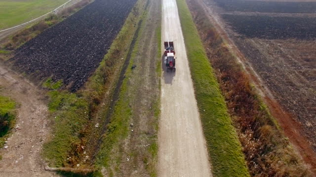 Aerial shot of a tractor driving on a dirt road