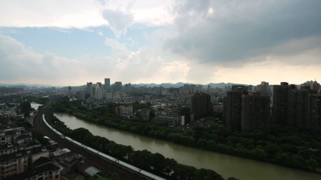 aerial shot of a train passing on downtown buildings,hangzhou - zhejiang province stock videos & royalty-free footage