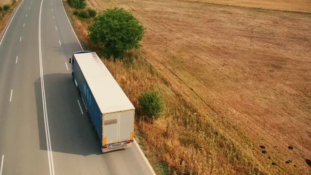 vídeos de stock e filmes b-roll de aerial shot of a trucks driving - transportation